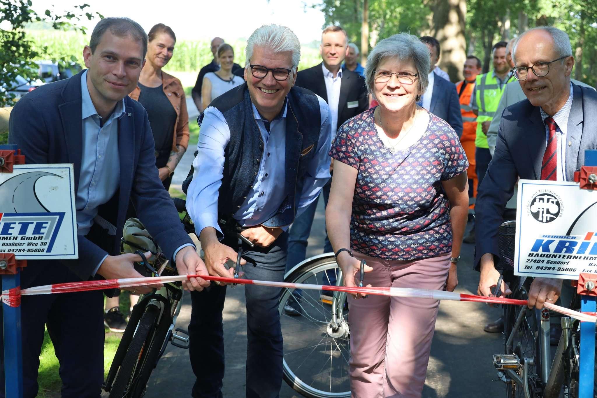 Der CDU-Landtagsabgeordnete Eike Holsten (von links), Ralf Goebel, Ursula Hoppe und Hermann Luttmann schneiden das Band für den Radweg durch. Foto: Henning Leeske