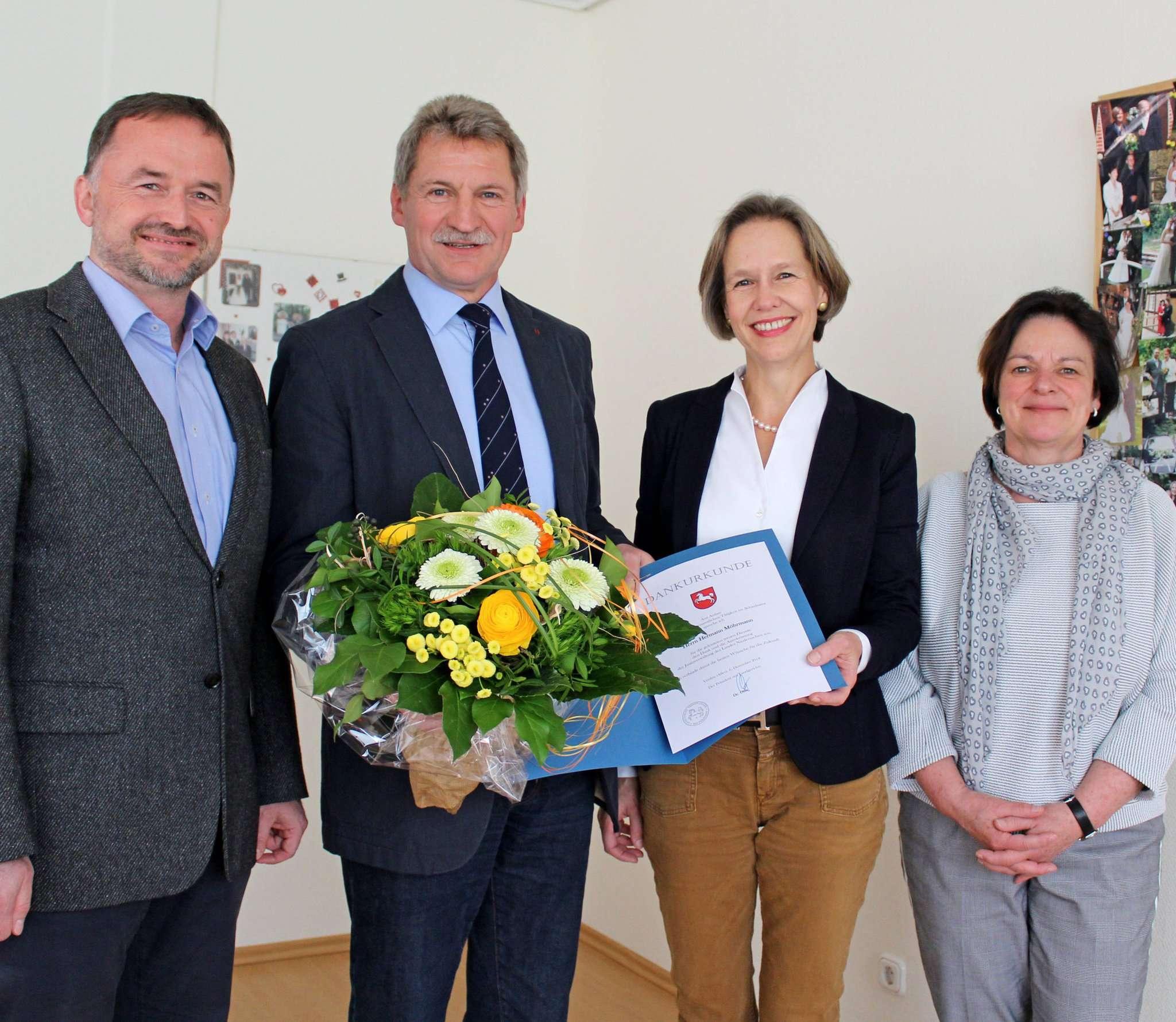 Samtgemeindebürgermeister Dirk Eberle (links), Maren von Frieling (rechts) und Clementine von Hahn gratulieren Hermann Möhrmann zu seinem Engagement. Foto: Ann-Christin Beims