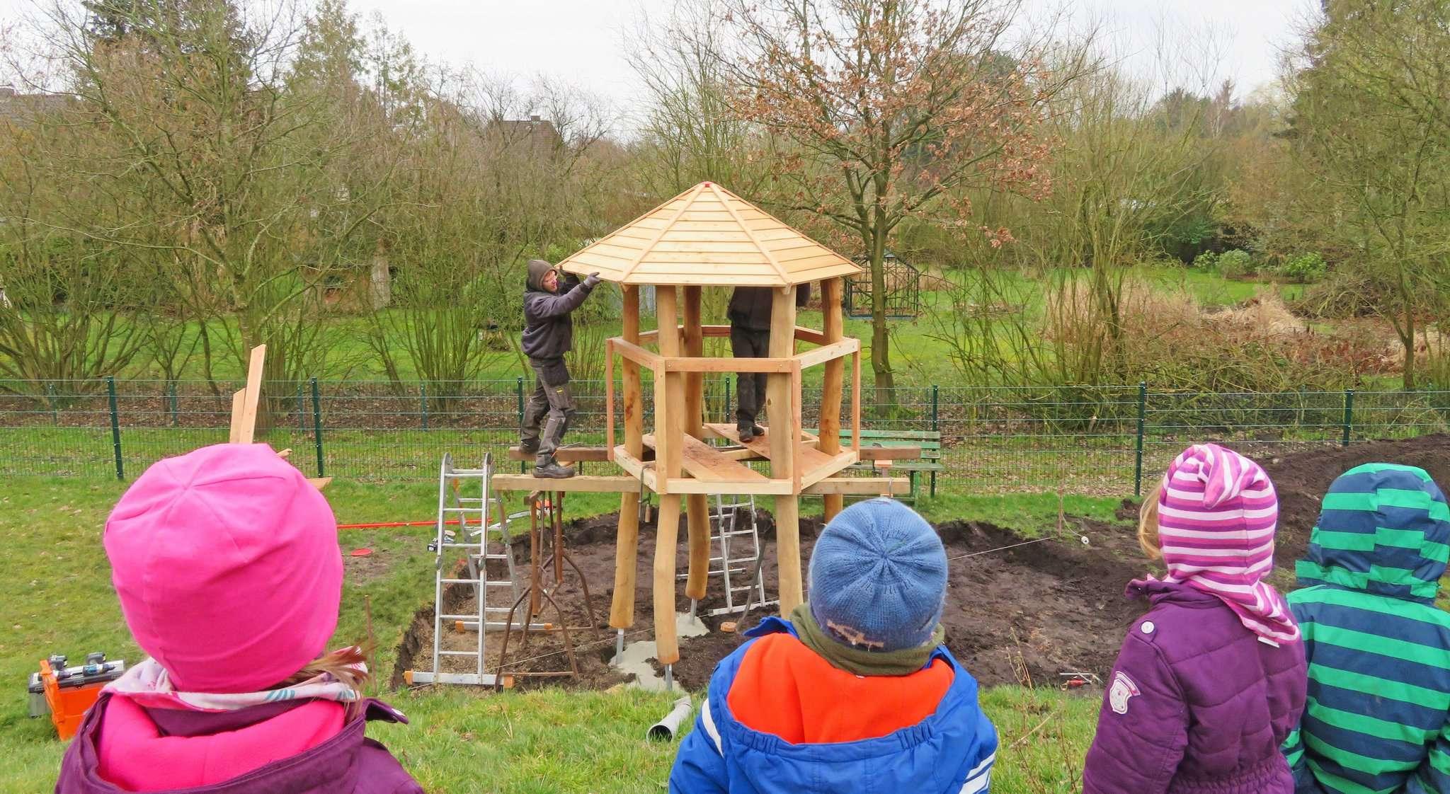 Fasziniert beobachten die Kinder den Fortschritt der Bauarbeiten am neuen Kletterturm, der im hinteren Teil des Geländes mittlerweile durch eine Hängebrücke mit ihrem Spielhügel verbunden ist. Fotos: Kindertagesstätte Löwenburg