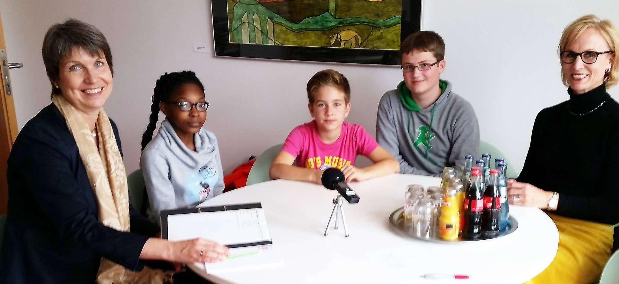 Erste Stadträtin Bernadette Nadermann (von links) beantwortet die Fragen von Deborah, Leander und Johann. Lehrerin Heike Mattick unterstützt ihre Schüler.