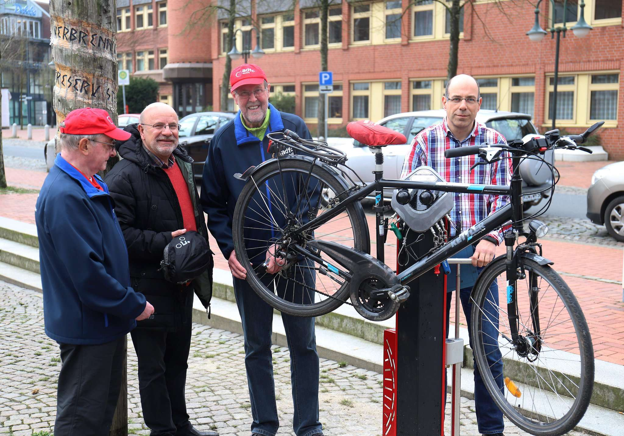 Aufgehängt und repariert: Wilfried Petschel (von links), Hans Eckert, Manfred Petersen und Uwe Knabe testen die neue Fahrrad-Reparaturstation.