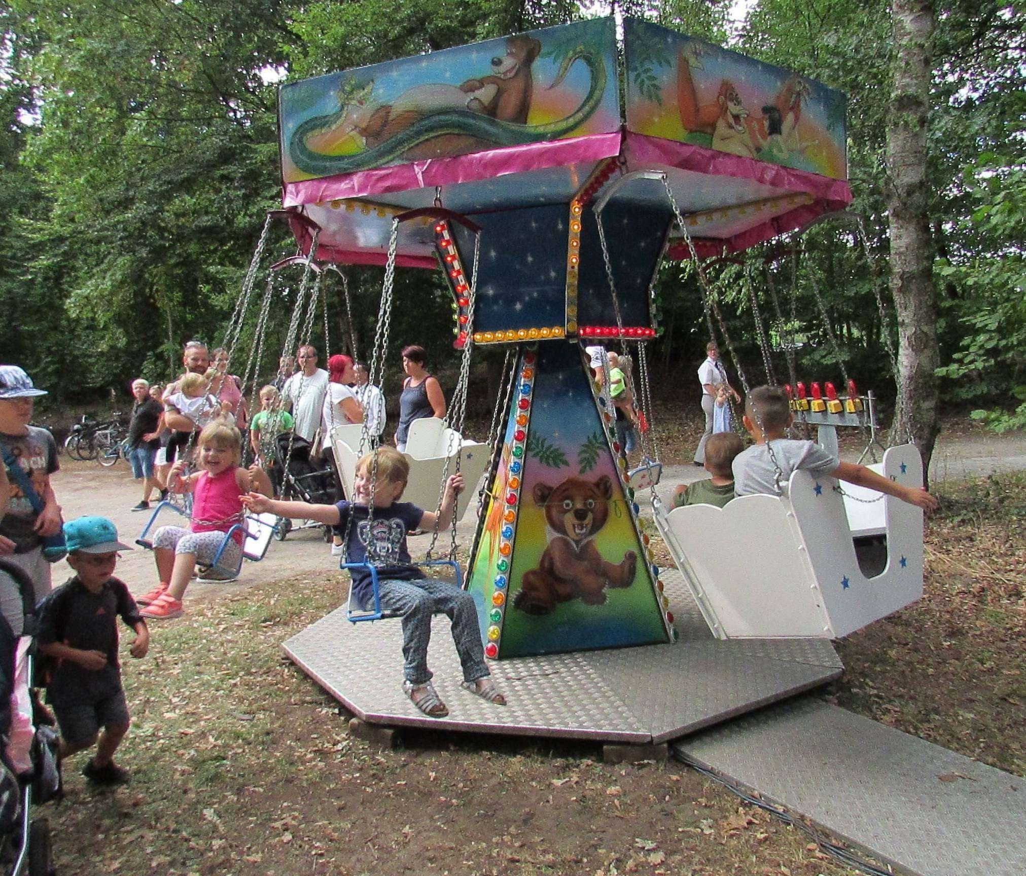 Die jüngeren Kinder freuen sich auf kostenlose Fahrten im Karussell.