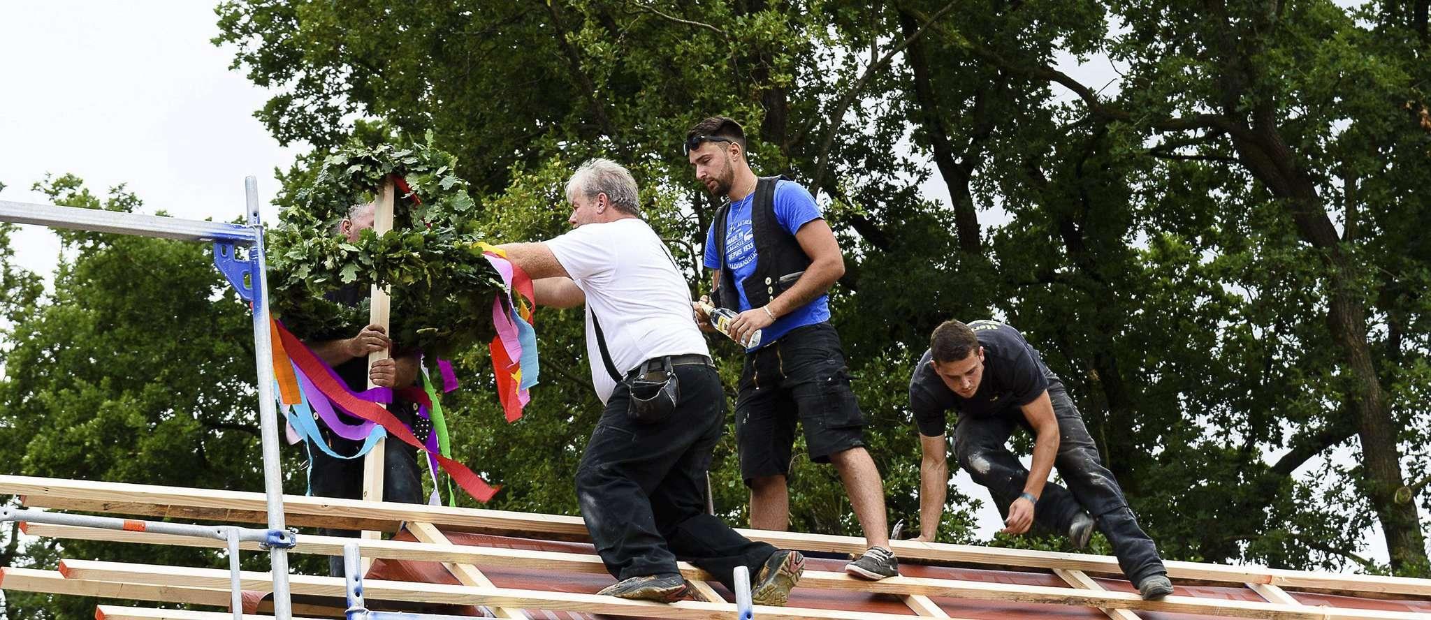 Helfer machen den Richtkranz auf dem Dach des neuen Krippenanbaus fest. Foto: Klaus-Dieter Plage