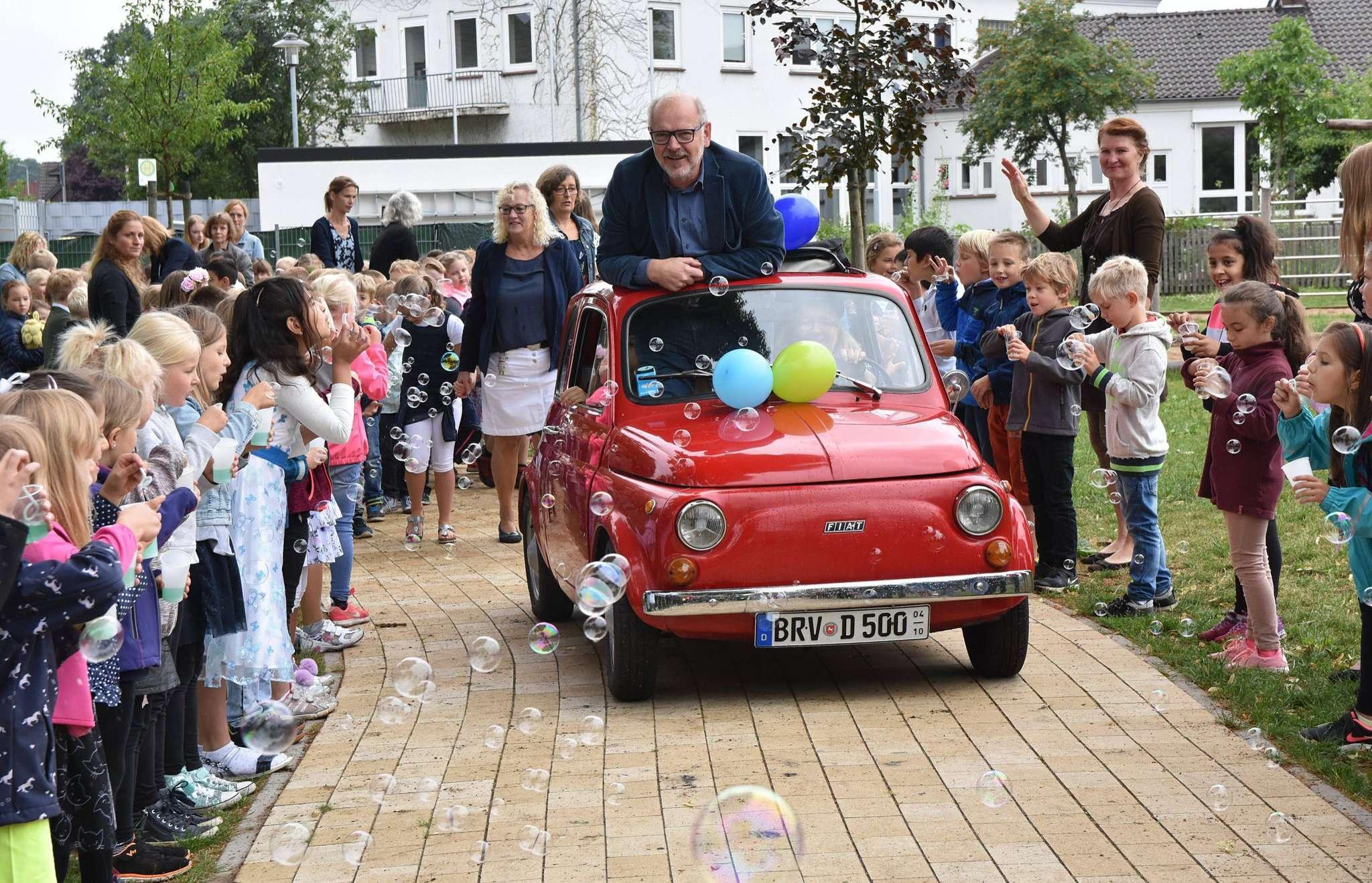 Lehrerin Dörte Dembski-Minssen hatte Bernd Tippel mit ihrem geschmückten Kleinwagen aus Zeven abgeholt und drehte mit ihm eine Ehrenrunde auf dem Schulhof, flankiert von Lehrern und Schülern und einem Seifenblasenmeer. Fotos: Heidrun Meyer