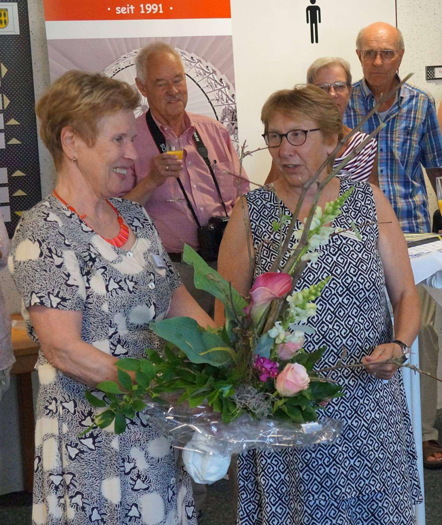 Käthe Dittmer-Scheele überreicht Rosemarie Ullmann einen Blumenstrauß.