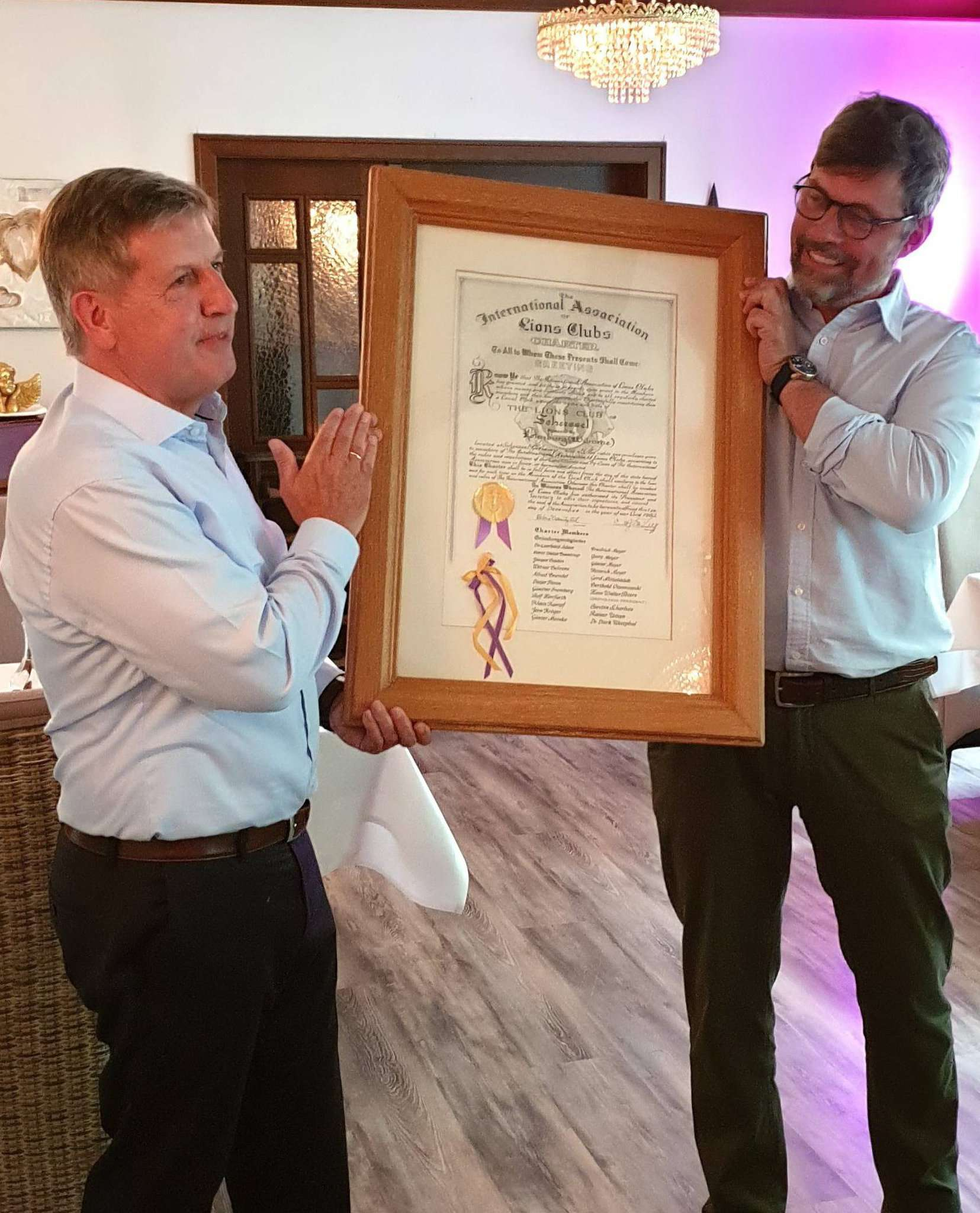 Der scheidende Präsident Jan Gerlach (rechts) übergibt die Scheeßeler Lions-Charterurkunde an seinen Nachfolger Rainer Windler.