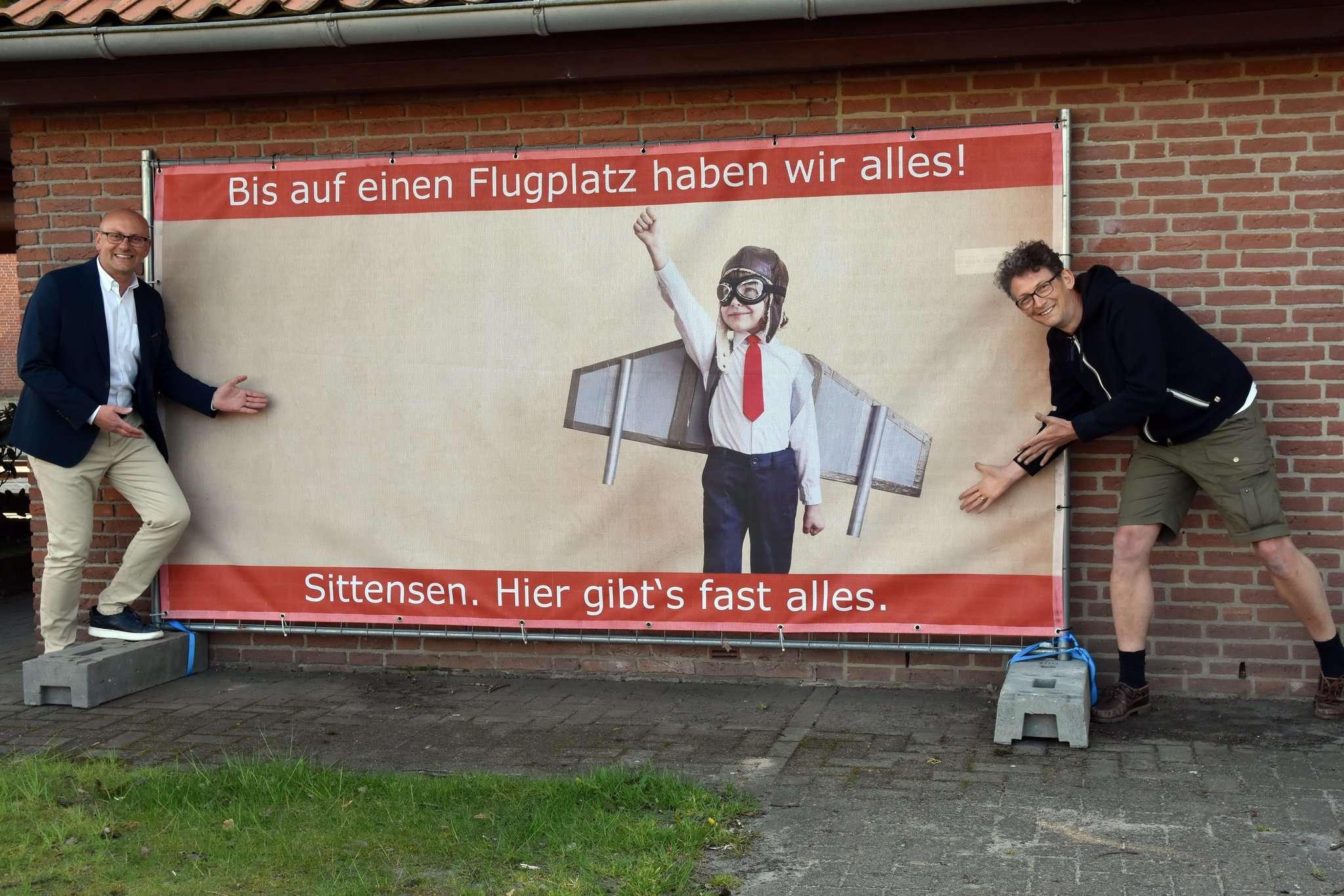 Torsten Wichern und Jens Schliwa vom Wir mit einem der auffälligen Plakate, das beim Busbahnhof hängt und mit einem markigen Spruch daherkommt. Foto: Heidrun Meyer