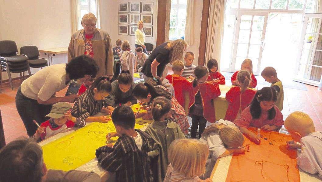 Künstler Willi Reichert schaut den kleinen Nachwuchsmalern über die Schultern, während diese die Fahnen für den Kultursommer