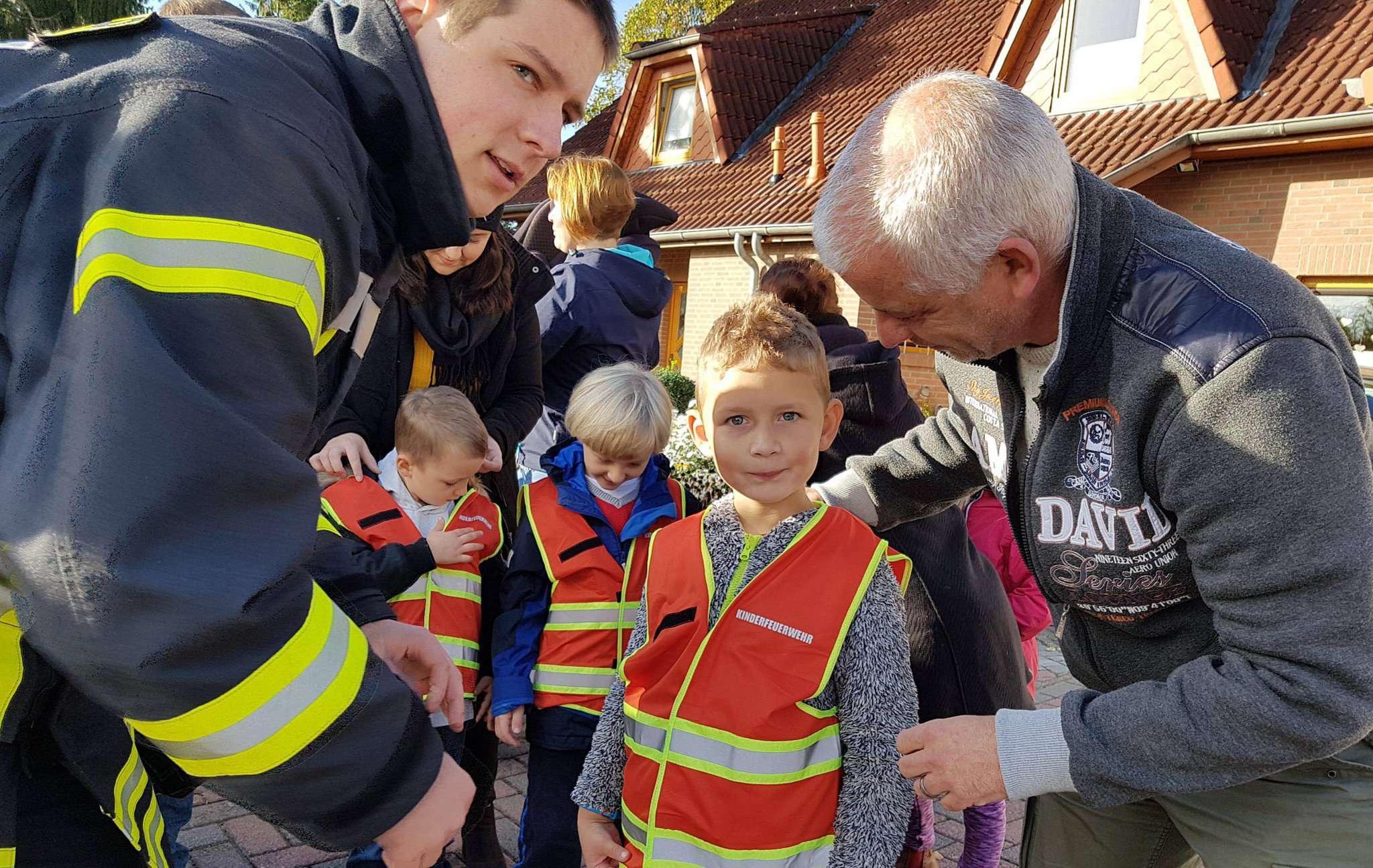 Papa Norman Till (rechts) und Jugendbetreuer Torben Böhrs mit Lasse, der jetzt zur Kinderfeuerwehr gehört und stolz die neue Weste präsentiert.