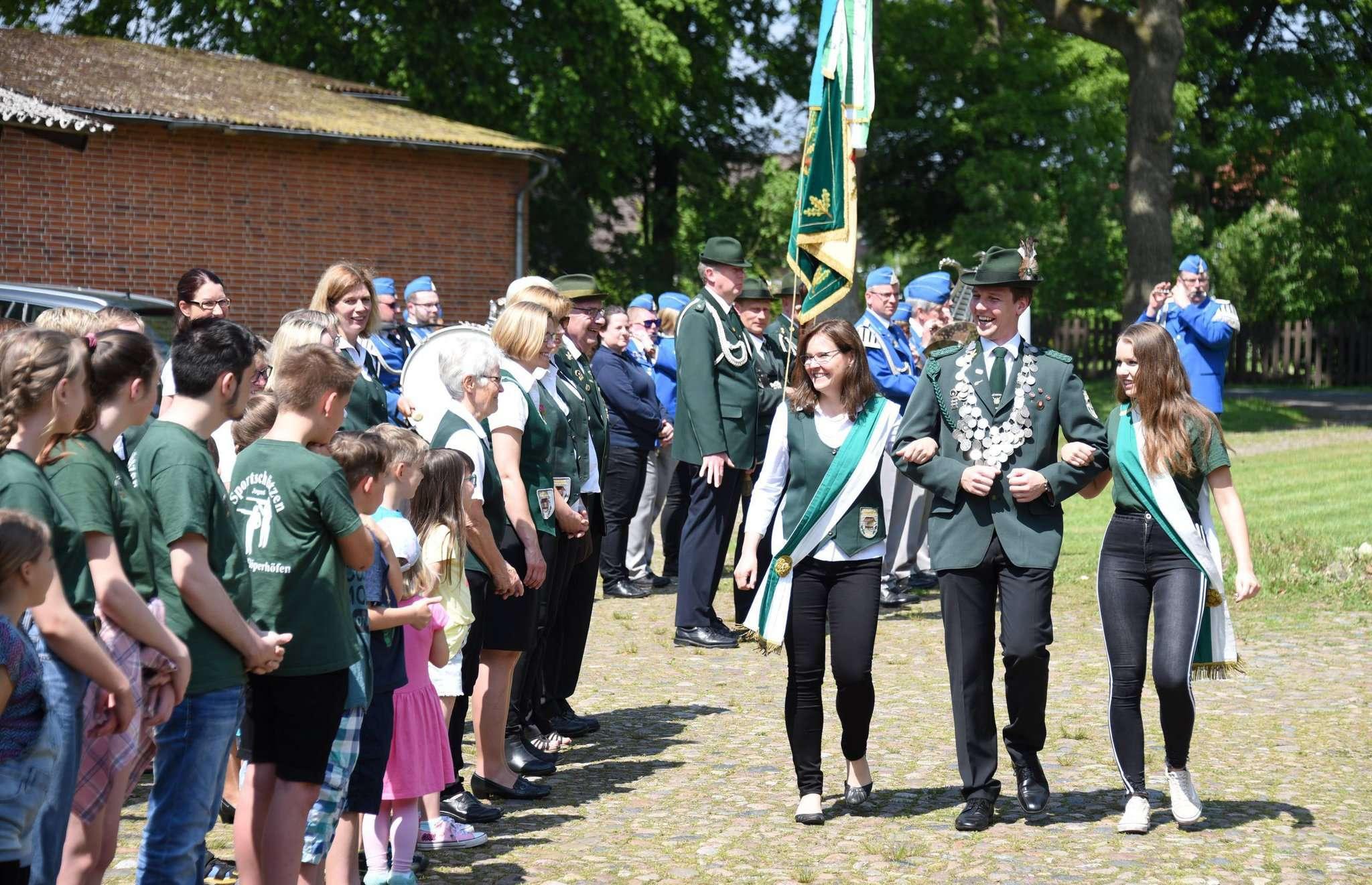 Schützenkönig Jan-Hendrik Müller schreitet mit den Ehrendamen die Formation ab.
