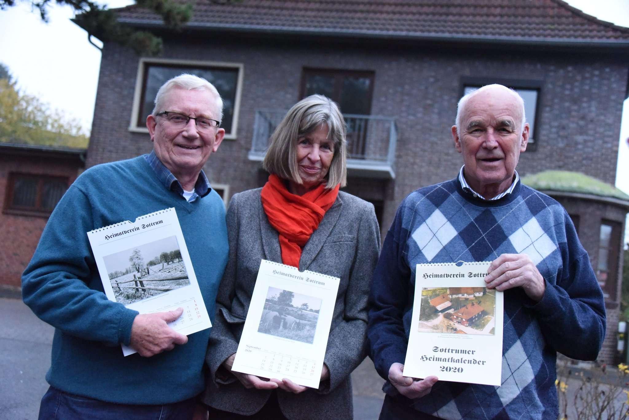 Hans-Georg Wiedemeyer (von links), Hanna Hildebrandt und Hans-Richard Buthmann vor einem der historischen Motive ihres Heimatkalenders: die ehemalige Gaststätte Hermann Plate.