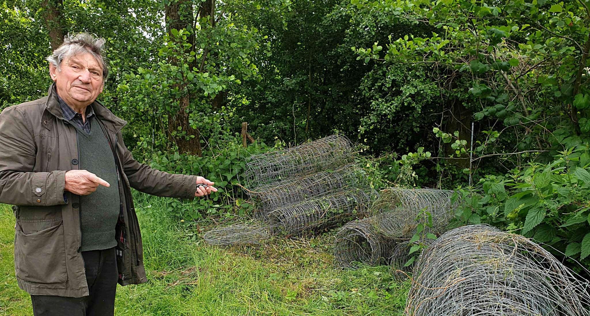 Siegfried Gässler vor dem Waldstück, der der Natur wieder zurückgeben wurde, mit dem abgebauten Zaun.