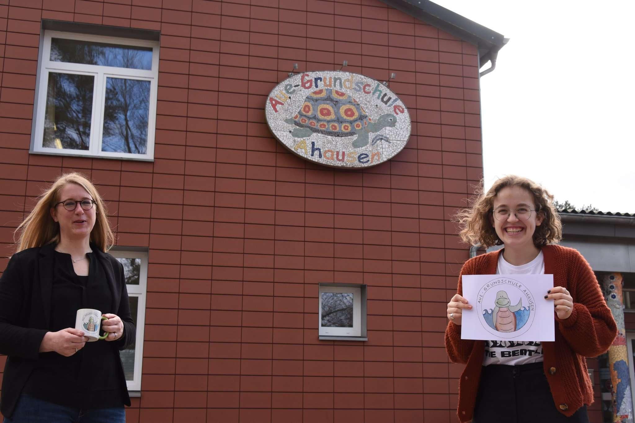 Nele Grabs (rechts) gestaltet das neue Logo für die Aue-Grundschule in Ahausen. Auch Schulleiterin Lavinia Wieland ist angetan von dem Werk, das auch auf den Tassen für die Erstklässler zu sehen ist.