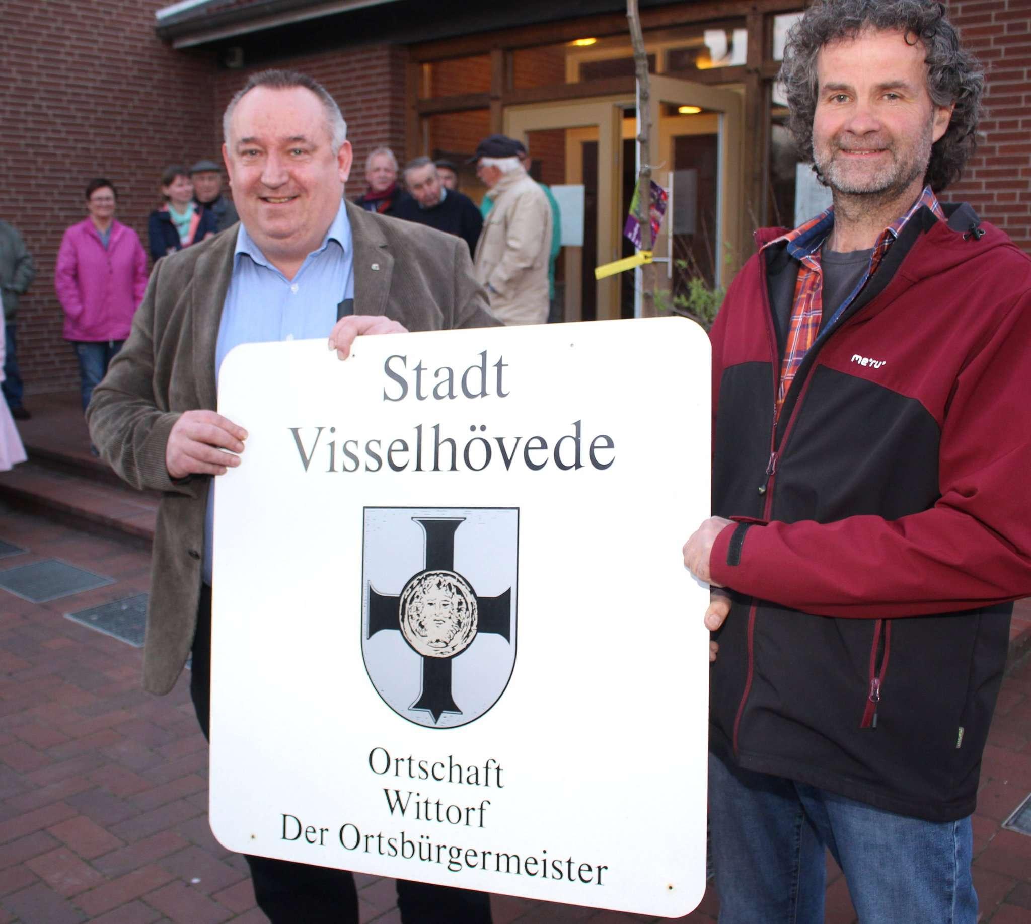 Die symbolische Übergabe des Schildes der Stadt Visselhövede von Willi Bargfrede (L) an den neuen Ortsbürgermeister Heiner Gerken. Fotos: Henning Leekse