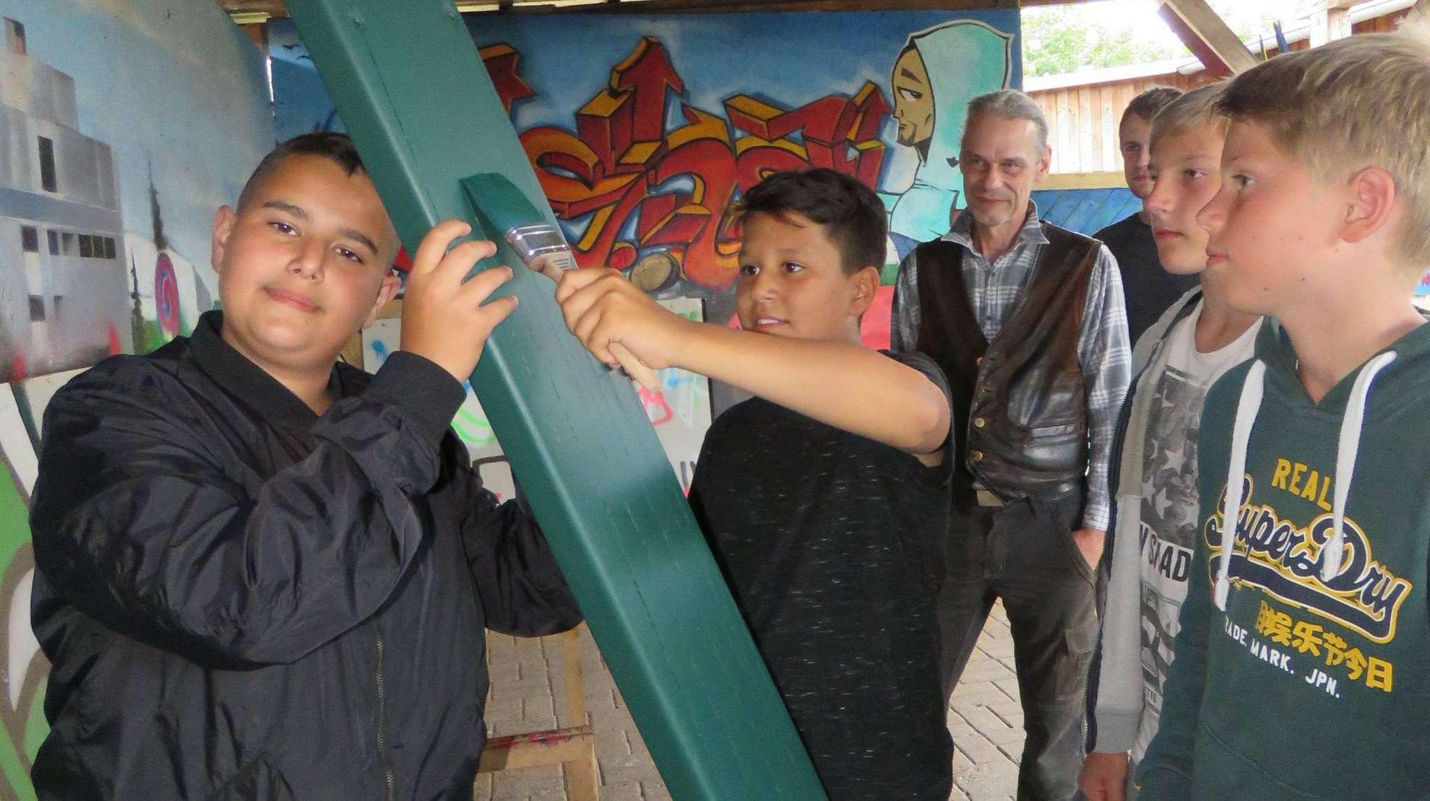 Frank Steinke (Hintergrund) zeigt Jungs den Umgang mit Werkzeug.  Foto: Elke Keppler-Rosenau
