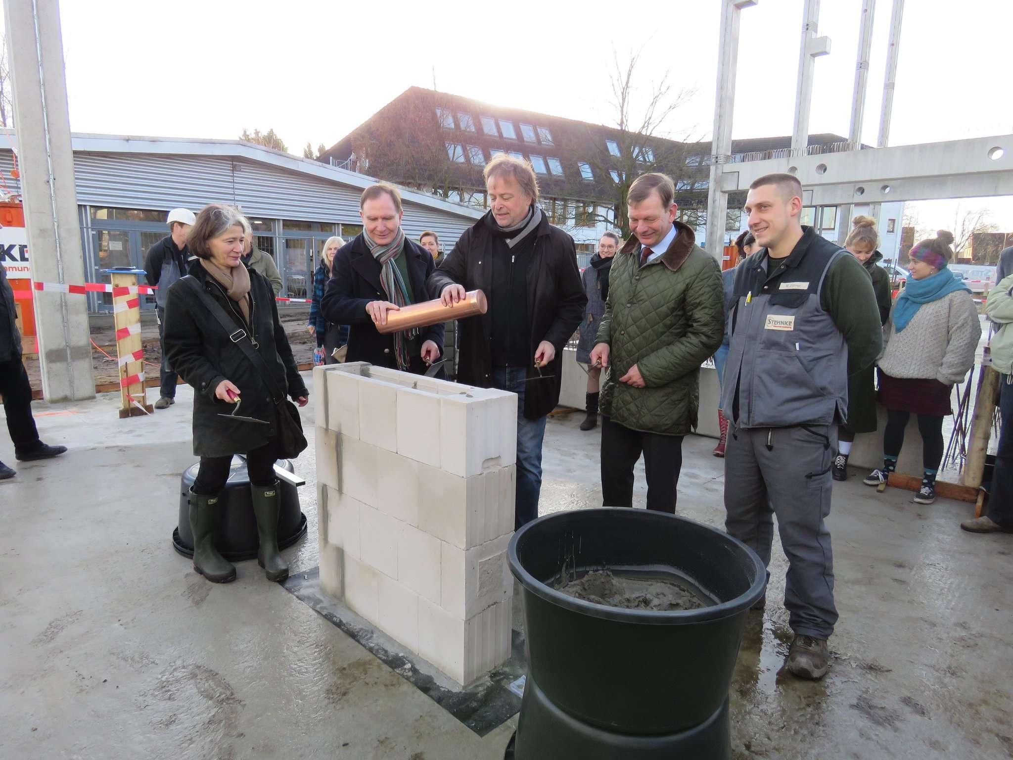 Nach Anweisung des Poliers legte der künstlerische Leiter der HKS, Ralf Rummel-Suhrcke (Mitte), die Zeitkapsel in den Grundstein für den neuen Forschungstrakt.  Foto: Elke Keppler-Rosenau