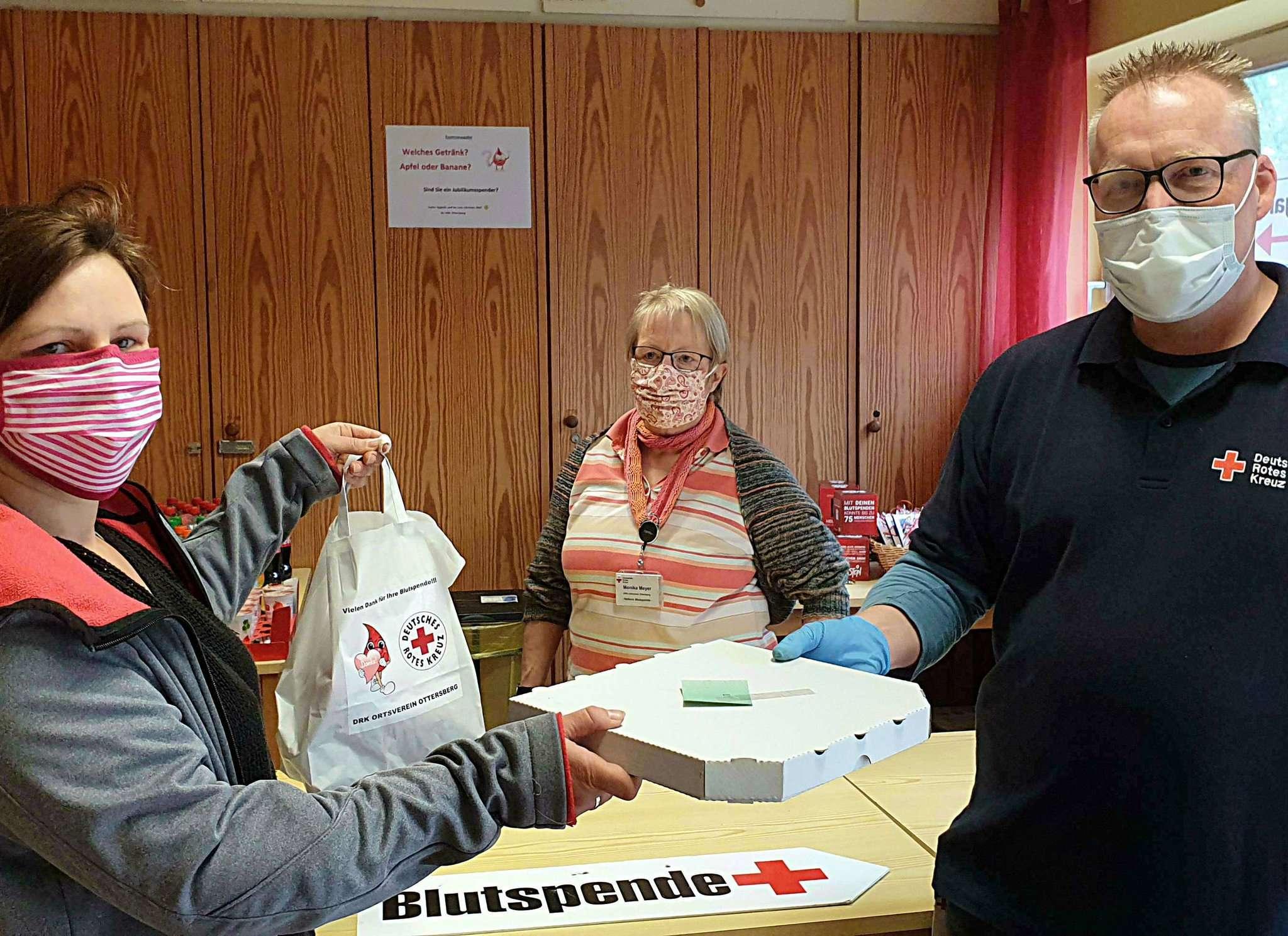 Stefan Asendorf händigt in Beisein von Monika Meyer (Mitte) Raphaela Rode eine Pizza aus.  Foto: Tobias Woelki