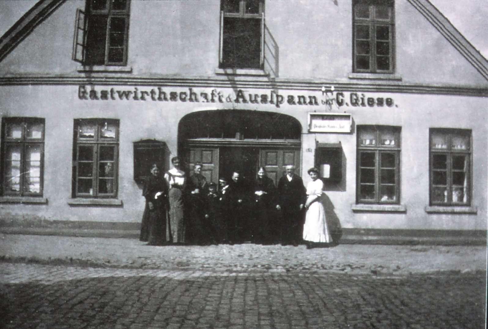 Das Gasthaus Giese in alten Zeiten. Die beiden Schaukästen am Eingang zeigen nicht etwa die Preise für Bier und Korn. Hier befanden sich vielmehr die öffentlichen Bekanntmachungen der Gemeinde. Da es noch kein Rathaus gab, wurden sie am privaten Domizil des Bürgermeisters angebracht.