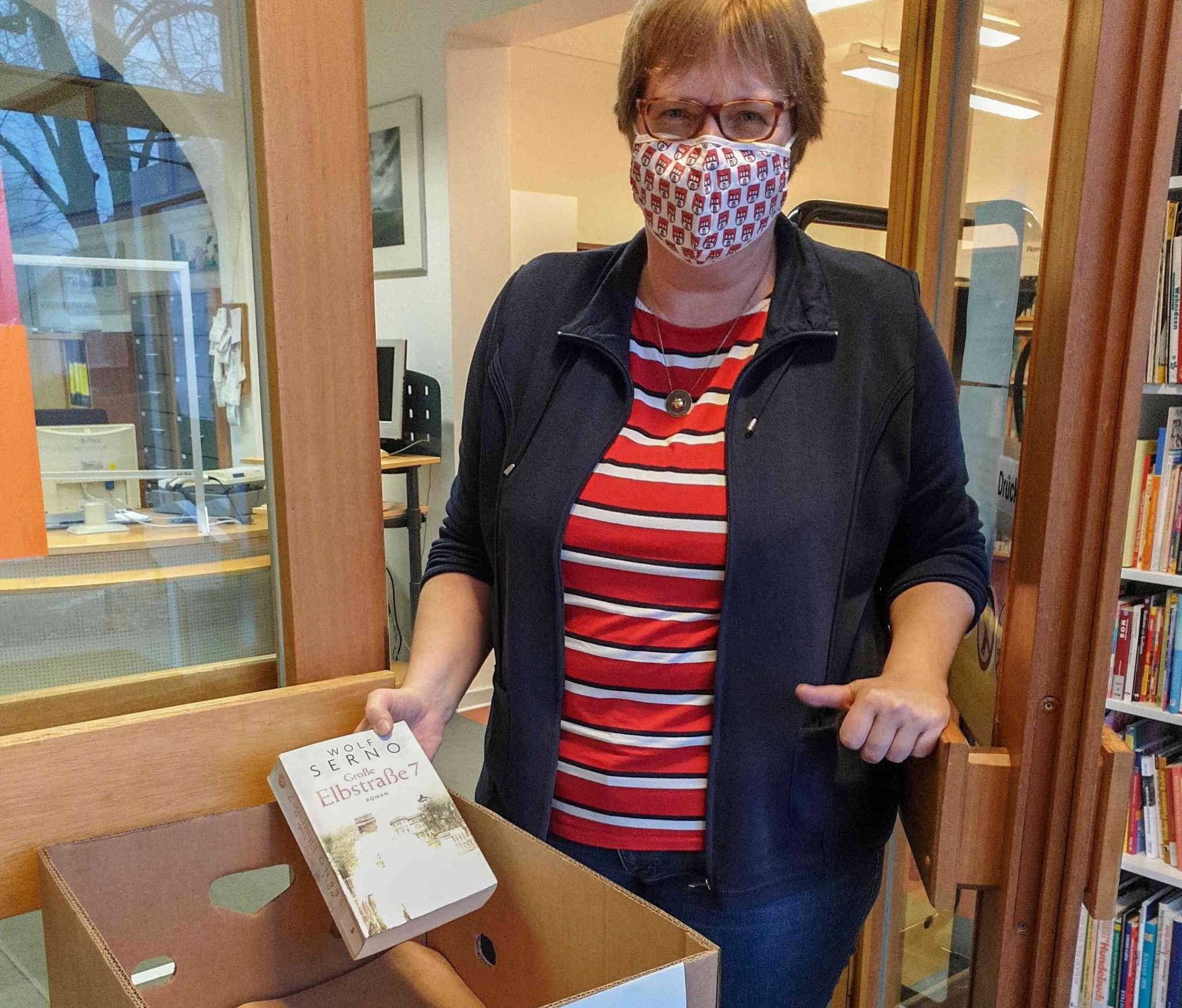 Karen Marheine erklärt den Bücherservice im Vorraum. Foto: Tobias Woelki