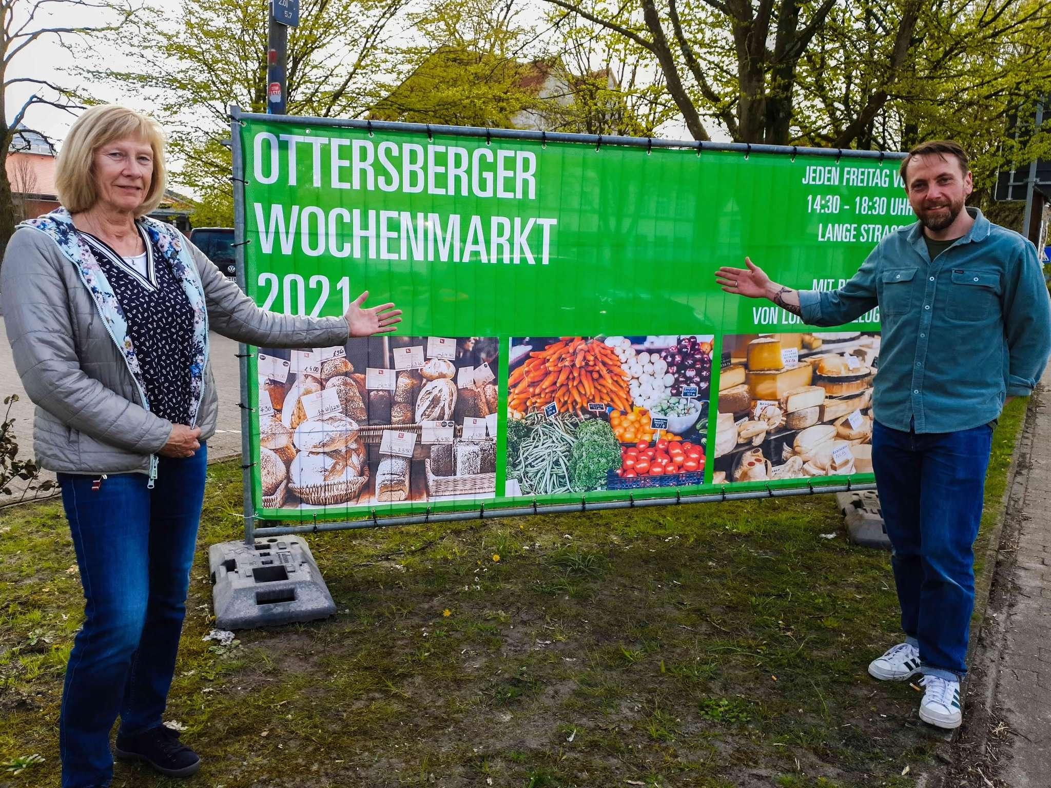 Gabriele Könnecke (li.) und Jesper Theis hängen Banner auf, die für den neuen Wochenmarkt werben. Foto: Tobias Woelki