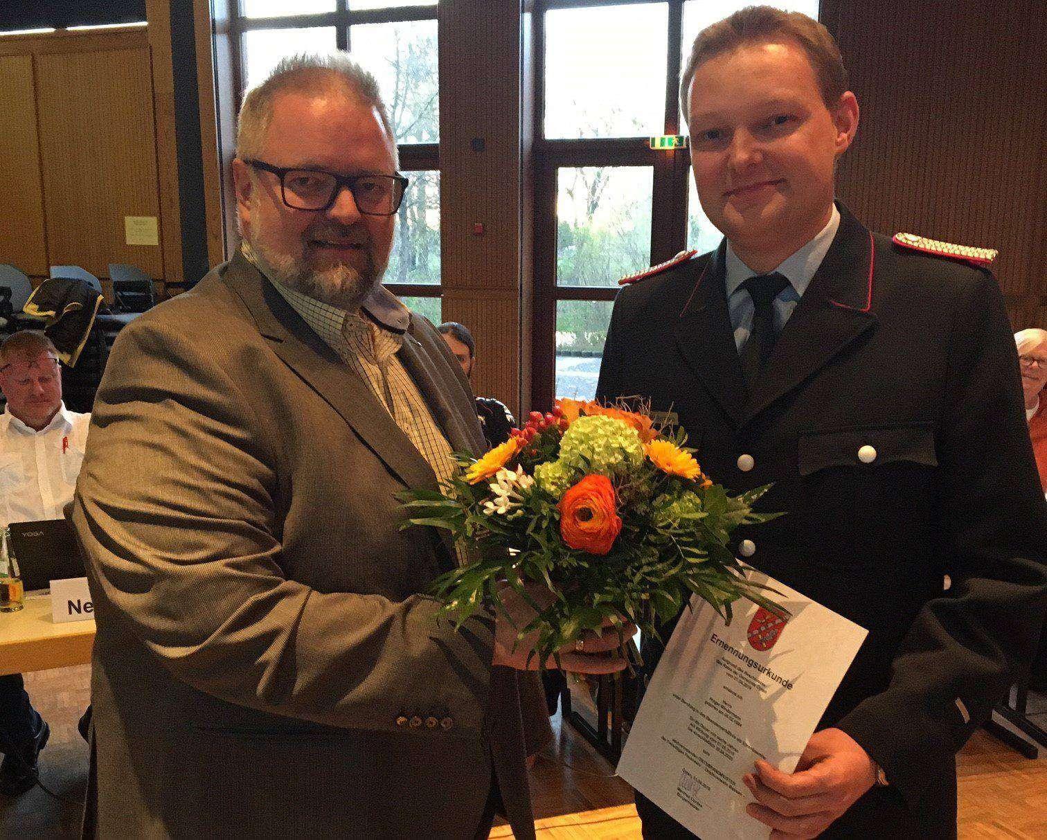 Oytens stellvertretender Bürgermeister Heiko Oetjen (links) überreicht Holger Mindermann Urkunde und Blumen.