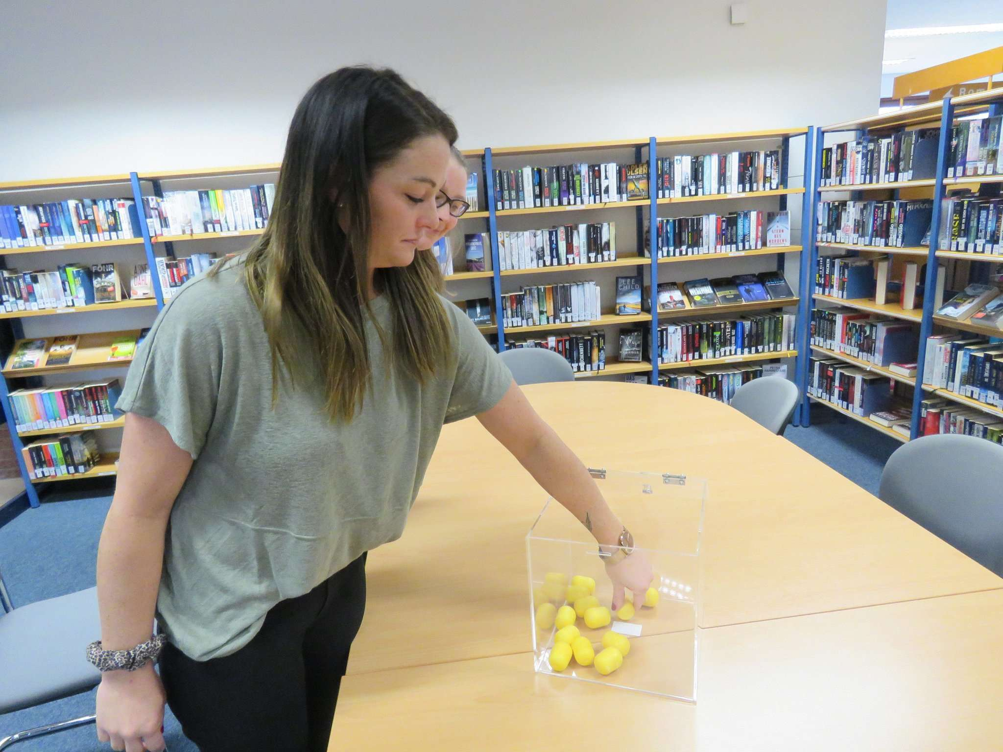 Rathaus-Mitarbeterin Lisa Bormann-Rajes (vorne) zog als Glücksfee zwei Kapseln mit Gewinnzetteln aus der Box, während Büchereileiterin Jaqueline Ballandis die Aktion überwachte. Foto: Elke Keppler-Rosenau