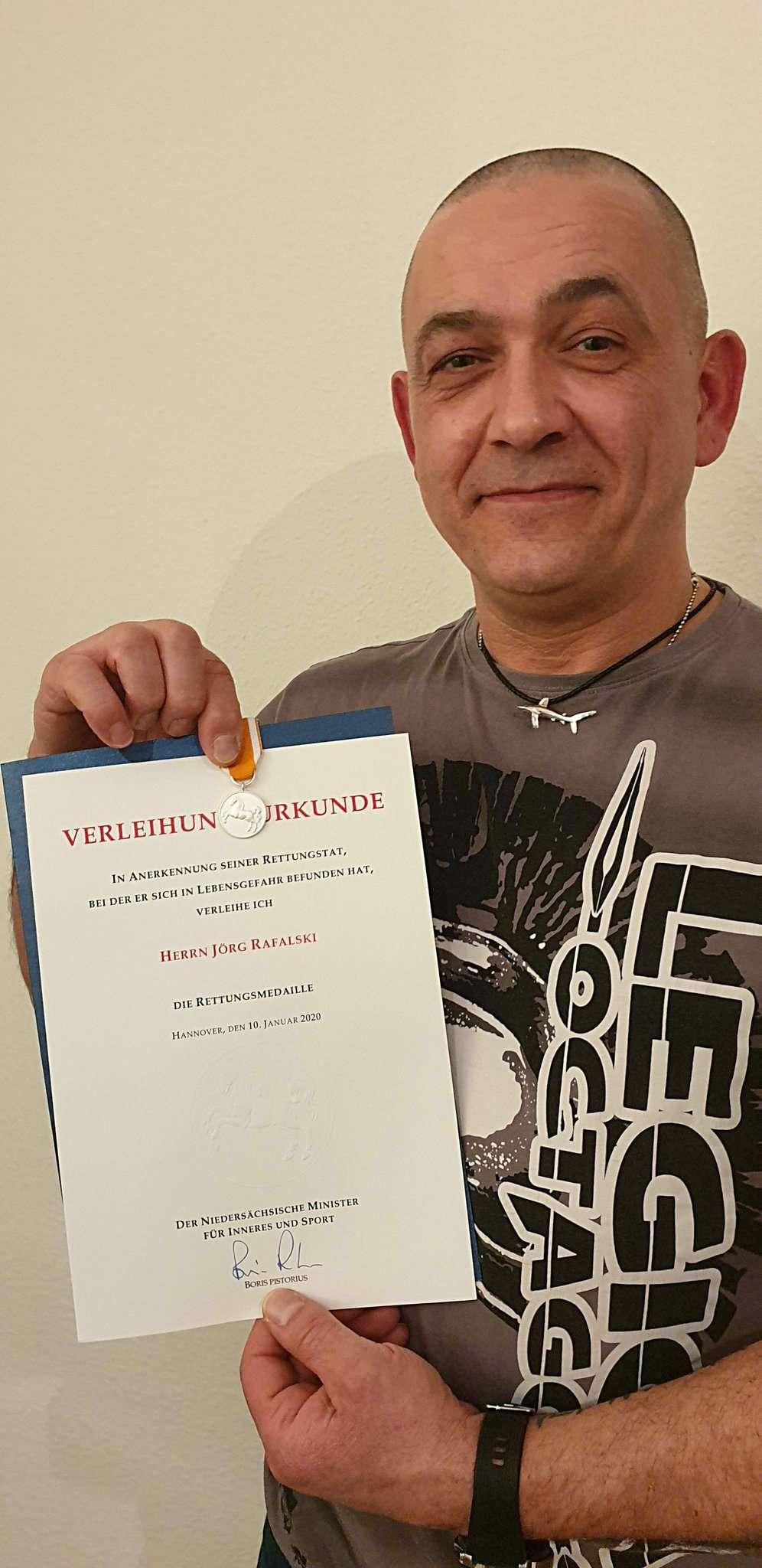 Jörg Rafalski mit Urkunde und Rettungsmedaille.  Foto Tobias Woelki