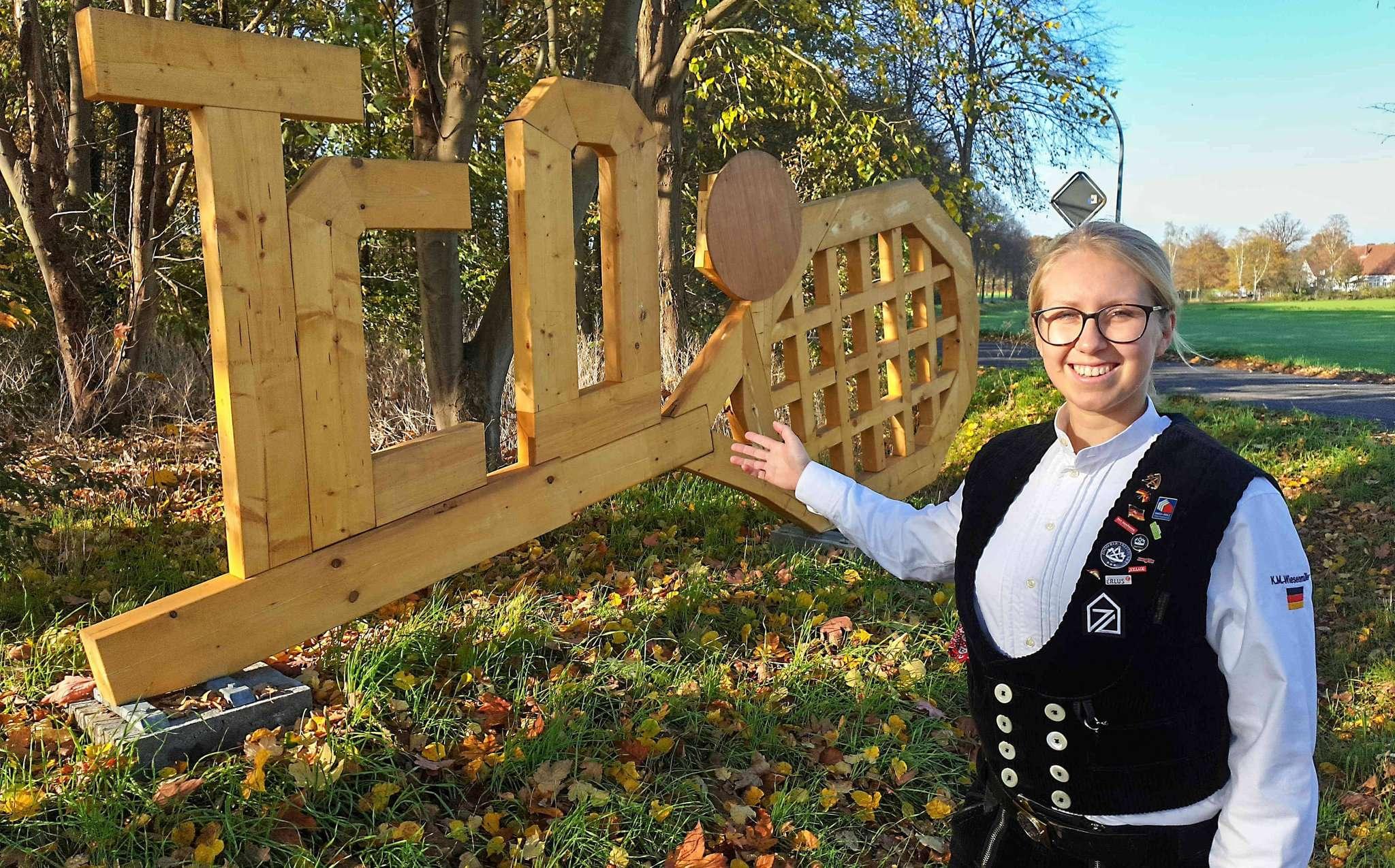 Katja Wiesenmüller mit selbst gebautem Holzemblem. Foto: Tobias Woelki