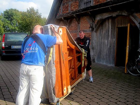 Mit Kraft und Fingerspitzengefühl wird der Korpus des Irmler-Flügels ins Brockwischenhus gebracht          Foto: Dierks