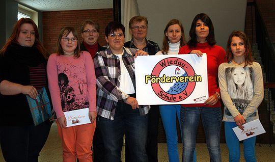 Die Teilnehmer des Wettbewerbs und die Mitglieder des Fördervereins sowie die Rektorin Annemarie Dollinger der Wiedau-Schule freuen sich über das neue Logo