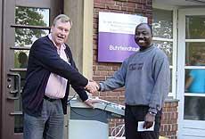 Claus Kock und Kingsley Ampeh bei der Übergabe der medizinischen Geräte vor dem Buhrfeindhaus des Diakonie-Krankenhauses in Rotenburg.