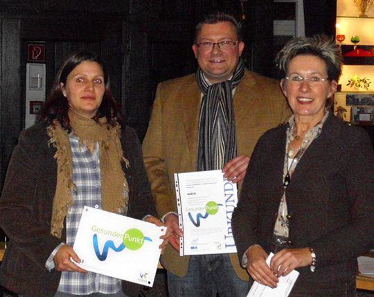 Linda Wiederhold von der Aleco-Supermarktkette erhält die Auszeichnung von Markus Luckhaus und Ute Scholz