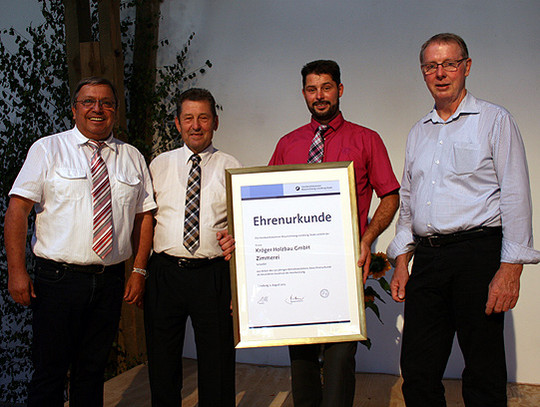 Kreishandwerksmeister Friedrich Lefers (links) und Obermeister Horst Fricke (rechts) überreichten eine Urkunde an Seniorchef Friedrich Kröger (Zweiter von links) und Geschäftsführer Volker Kröger    Foto. Ricci